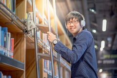Young Asian man choosing book using ladder in library. Young Asian man choosing book in bookshelf using ladder in library, male student dressed in casual style Stock Photo