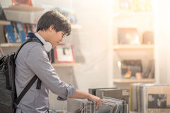 Young Asian man choosing disc in music shop. Young Asian man with headphones choosing disc in music shop, urban lifestyle concepts stock photo
