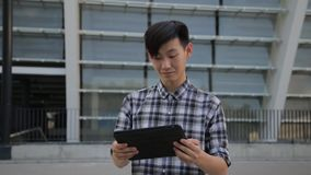 Young asian man in city using tablet computer PC outdoors. Asian man in city using tablet computer PC outdoors wearing checkerboard shirt stock video