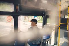 Young  asian man on commute travel to work sitting in bus or tra. In Stock Image