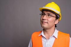 Young Asian man construction worker wearing eyeglasses against g. Studio shot of young Asian man construction worker wearing eyeglasses against gray background royalty free stock photography
