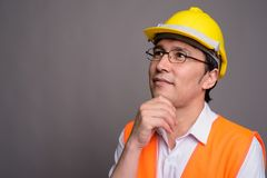 Young Asian man construction worker wearing eyeglasses against g. Studio shot of young Asian man construction worker wearing eyeglasses against gray background stock images