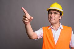 Young Asian man construction worker wearing eyeglasses against g. Studio shot of young Asian man construction worker wearing eyeglasses against gray background royalty free stock photos