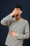 Young Asian man covering his face by palm Royalty Free Stock Images