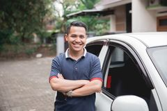 Standing in front of car. male taxi driver. Young asian man crossed arm standing in front of his car. taxi driver stock images