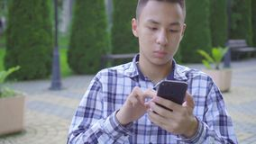 Young asian man disabled in a wheelchair in the park and uses a smartphone stock video footage