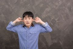 Young asian man disgusted young man plugging his ears to refuse. Listening background Royalty Free Stock Photography