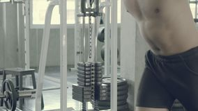 Young asian man doing cable rope triceps pull up exercise for bodybuilding in the gym