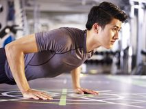 Young asian man doing push-ups in gym royalty free stock photos