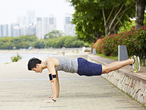 Young asian man doing pushups in park royalty free stock photos