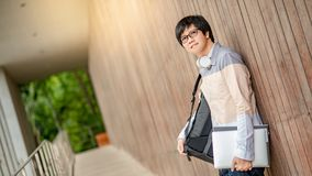Asian student man carrying backpack in college. Young Asian man dressed in casual style carrying backpack and holding file and laptop computer in university Stock Images