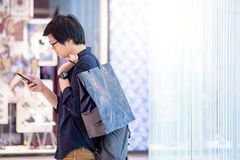 Young Asian man holding blue shopping bag in department store. Young Asian man dressed in casual style holding blue shopping bag using smartphone near retail Stock Photos