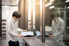 Young Asian man university student opening book in library. Young Asian man dressed in casual style opening book in library. Male university student research Royalty Free Stock Images