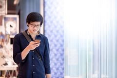 Young Asian man using smartphone in department store Stock Photography