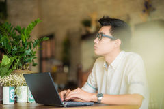 Young asian man drinking coffee in cafe and using laptop compute royalty free stock photography