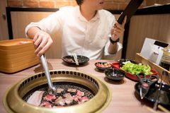 Young Asian man eating Korean Barbecue buffet in restaurant stock photo