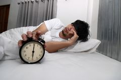 Young Asian man with eye mask wake up and stop alarm clock on the bed.  royalty free stock photography