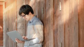 Asian man university student using laptop in college. Young Asian man with eyeglasses using laptop computer standing by wooden wall in college building. Male Stock Photography