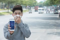 Showing red alert notification. Young Asian man in face mask showing red alert notification on smartphone Royalty Free Stock Photos