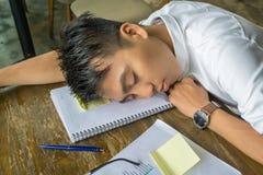 Young Asian man falling asleep on document stock photos