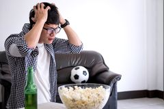 Young Asian Man fanclub watching soccer match on tv and cheering. Football team, celebrating with beer and popcorn at home, sports and entertainment concept Stock Images
