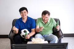 Young Asian Man and father watching soccer match on tv and cheer. Ing football team, celebrating with beer and popcorn at home, sports and entertainment concept Royalty Free Stock Photography