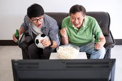 Young Asian Man and father watching soccer match on tv and cheer. Ing football team, celebrating with beer and popcorn at home, sports and entertainment concept Stock Image