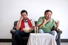 Young Asian Man and father watching soccer match on tv and cheer. Ing football team, celebrating with beer and popcorn at home, sports and entertainment concept Stock Photo