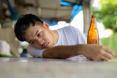 Young Asian man getting drunk in the streets outdoors stock image