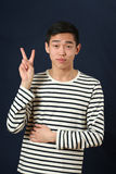 Young Asian man giving the victory sign Stock Photography