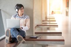 Young Asian student man using laptop in college. Young Asian man with glasses and headphones using laptop computer and listening to music during self-learning Royalty Free Stock Image