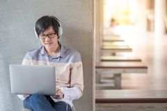 Young Asian student man using laptop in college. Young Asian man with glasses and headphones using laptop computer and listening to music during self-learning Stock Images