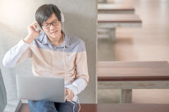 Young Asian student man using laptop in college. Young Asian man with glasses and headphones using laptop computer and listening to music during self-learning Royalty Free Stock Photo