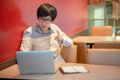 Asian man wearing using laptop in college. Young Asian man with glasses pointing his hand while using laptop computer in college. Male university student doing Stock Photo