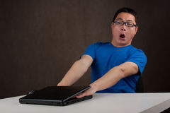 Young asian man got his hands stuck in laptop Royalty Free Stock Image