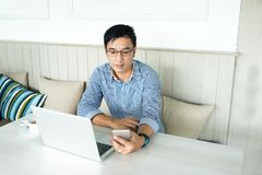 Young Asian man hand hold eye glasses looking out of window, Casual professional entrepreneur working-in out of office in cafe or. Coffee shop, modern lifestyle stock images