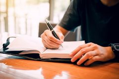 Young asian man hand writing on notebook. Young asian man hand writing on notebook Royalty Free Stock Photography