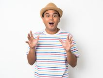 Young Asian man with hat feels shock and surprise with overly face expression. Asian man with hat feels shock and surprise with overly face expression royalty free stock image