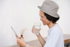 Young asian man with hat and glasses smile at tablet or laptop while holding a glass of water royalty free stock photography