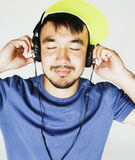 Young asian man in hat and headphones listening music on white b Stock Photos