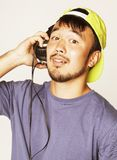 Young asian man in hat and headphones listening Royalty Free Stock Photo