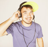 Young asian man in hat and headphones listening music on white background Royalty Free Stock Photography