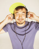Young asian man in hat and headphones listening music on white background Stock Photo