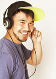 Young asian man in hat and headphones listening music on white background Stock Image