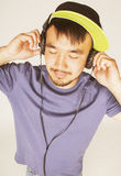 Young asian man in hat and headphones listening music on white background Royalty Free Stock Photo