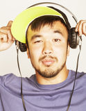 Young asian man in hat and headphones listening music on white background Royalty Free Stock Images