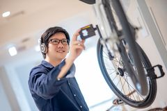 Young Asian man looking for bicycle in bike shop stock photo