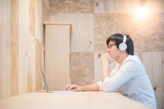 Young Asian man with headphones listening to music. Young Asian happy man with headphones listening to music and working on modern laptop computer in vintage Royalty Free Stock Image