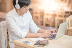 Young Asian man with headphones listening to music. Young Asian happy man with headphones listening to music and working on modern laptop computer in vintage Royalty Free Stock Photo