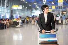 Young asian man with luggage in airport terminal Royalty Free Stock Images
